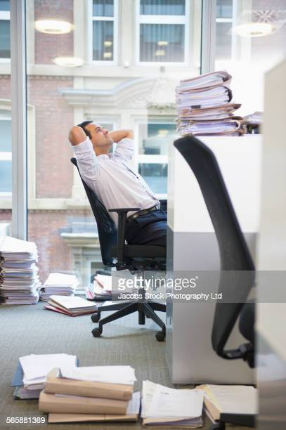 Mixed race businessman thinking at office cubicle