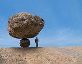Mixed race businessman under risky balancing boulder