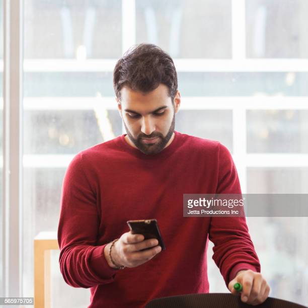 Mixed race businessman using cell phone in office