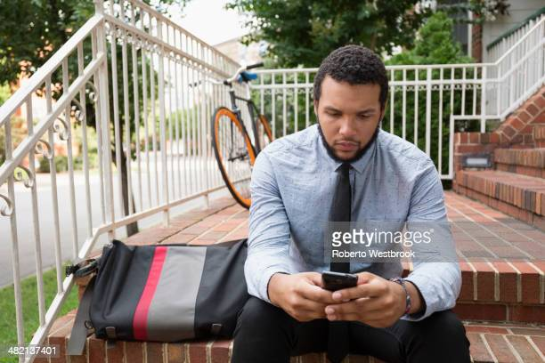 Mixed race businessman using cell phone on front stoop
