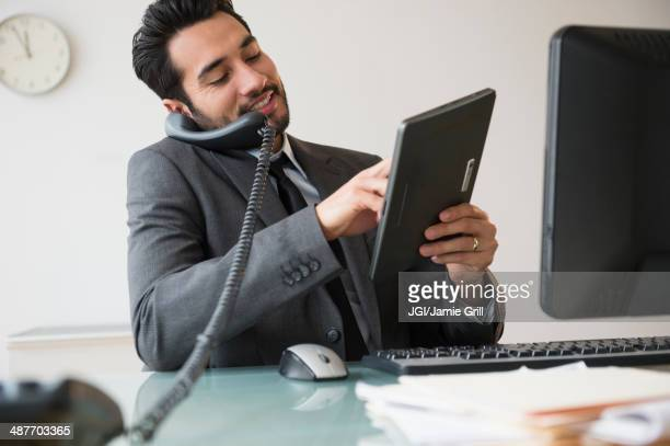 Mixed race businessman using digital tablet on telephone