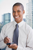 Mixed race businessman using electronic organizer