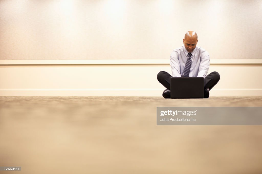 Mixed race businessman using laptop on floor : Stock Photo