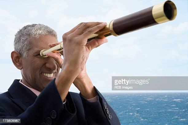 Mixed race businessman using telescope
