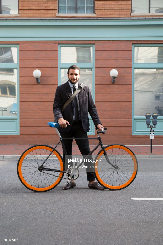 Mixed race businessman with bicycle on city street