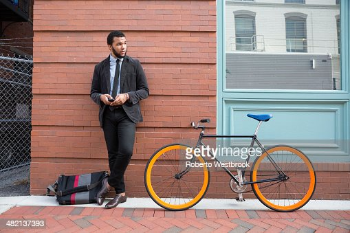 Mixed race businessman with bicycle on urban sidewalk