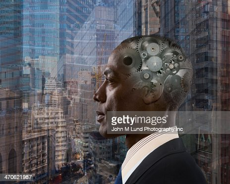 Mixed race businessman with gears in head : Stock Photo