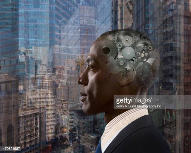 Mixed race businessman with gears in head
