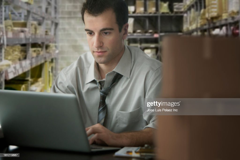 Mixed race businessman working in storage closet : Stock Photo