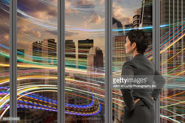 Mixed race businesswoman admiring light streams outside window