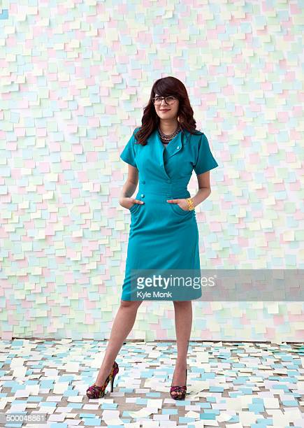 Mixed race businesswoman by wall of sticky notes