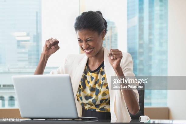 Mixed race businesswoman cheering at laptop at office desk