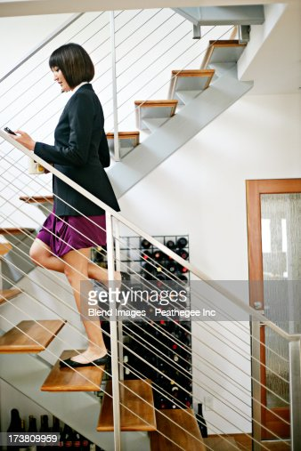 Mixed race businesswoman climbing staircase : Stock Photo