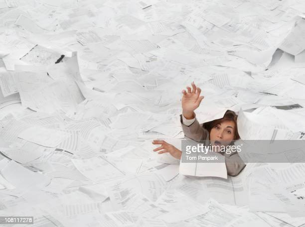 Mixed race businesswoman drowning in paperwork