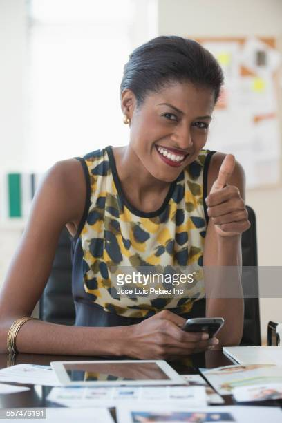 Mixed race businesswoman giving thumbs up at desk in office