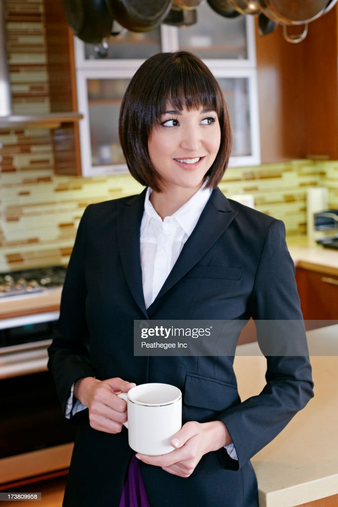 Mixed race businesswoman having coffee in kitchen : Stock Photo