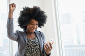 Mixed race businesswoman holding cell phone and cheering