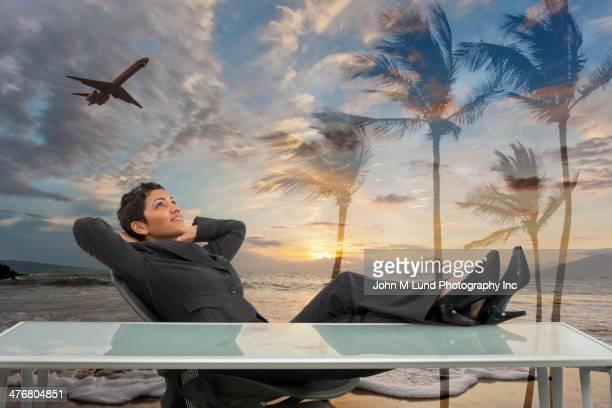 Mixed race businesswoman imagining tropical beach