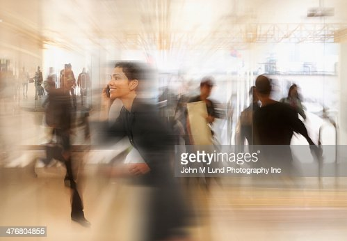 Mixed race businesswoman in busy workplace : Stock Photo