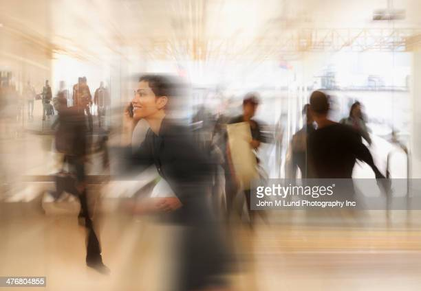Mixed race businesswoman in busy workplace