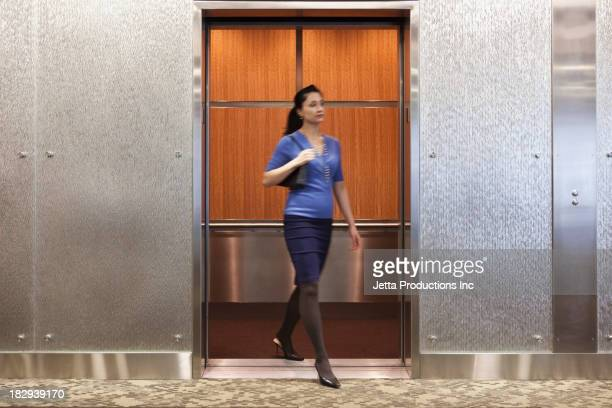 Mixed race businesswoman in elevator
