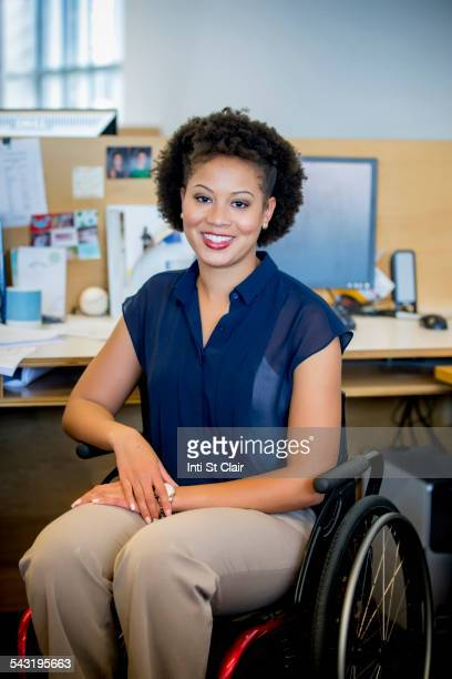 Mixed race businesswoman in wheelchair at office desk