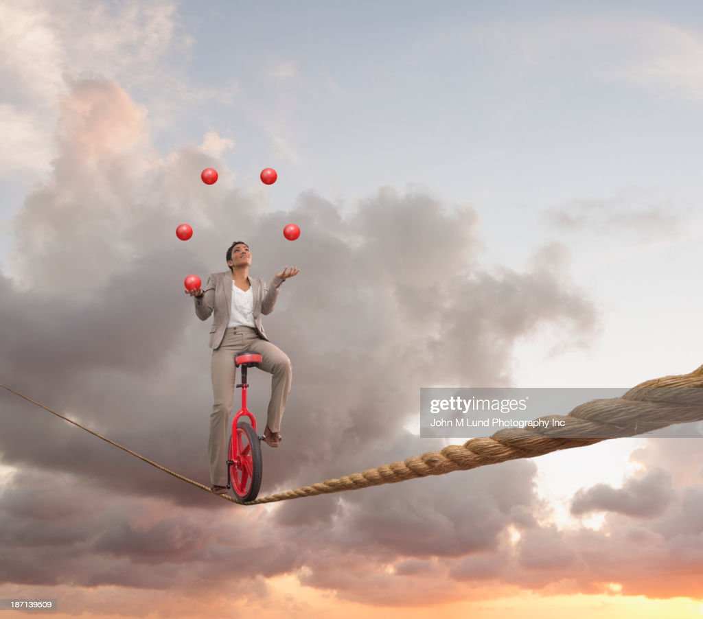 Mixed race businesswoman juggling on tightrope on unicycle : Stock Photo