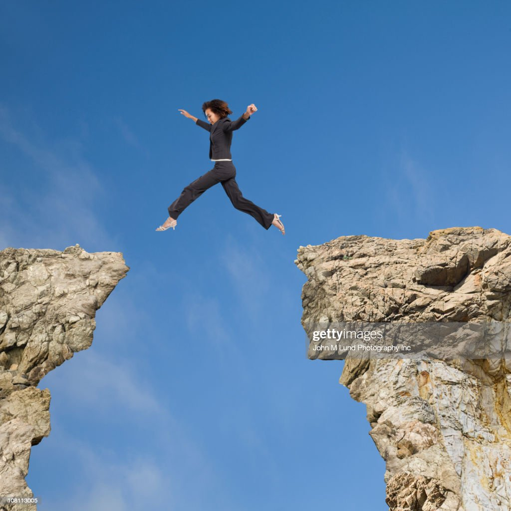 Mixed race businesswoman jumping over gap between cliffs for Jump the gap