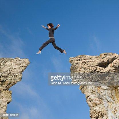 Mixed race businesswoman jumping over gap between cliffs : Stock Photo