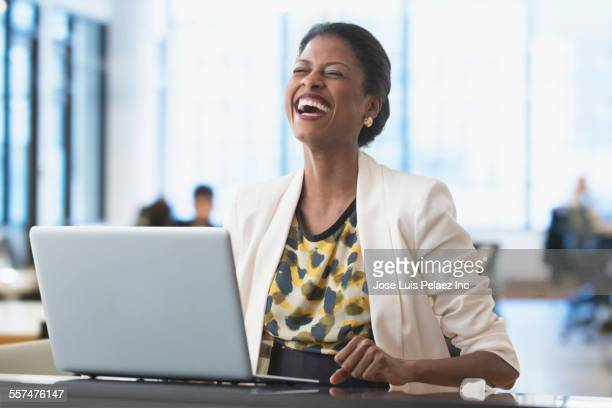 Mixed race businesswoman laughing at laptop at office desk