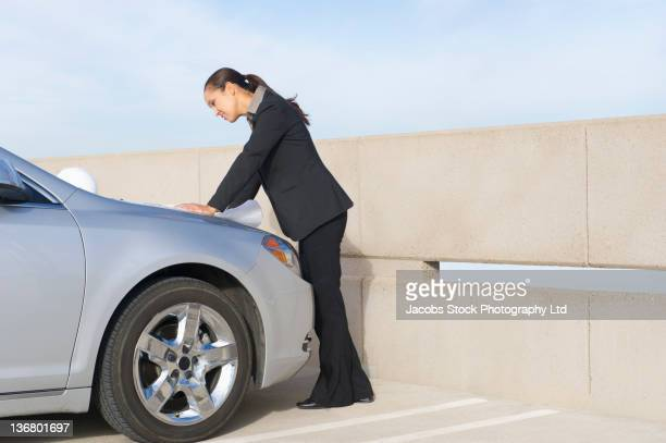 Mixed race businesswoman looking at blueprints in parking lot