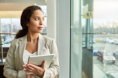 Portrait shot of pensive mixed race businesswoman looking out panoramic window of spacious office while taking short break from work