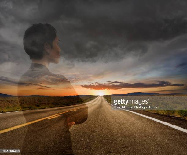 Mixed race businesswoman on remote road under sunset sky