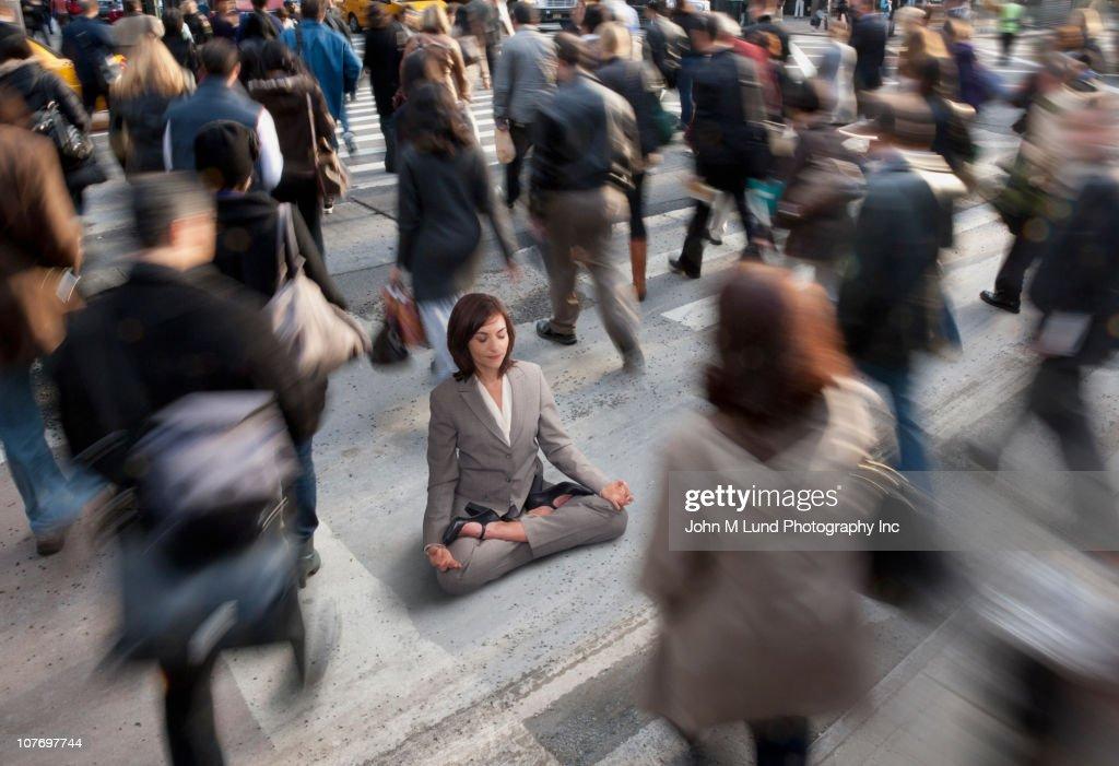 Mixed race businesswoman practicing yoga in busy urban crosswalk
