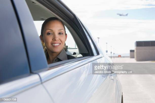Mixed race businesswoman riding in car