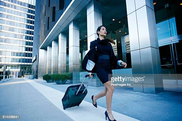 Mixed race businesswoman rolling baggage in city