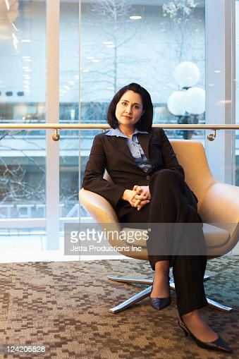 Mixed race businesswoman sitting in office : Stock Photo
