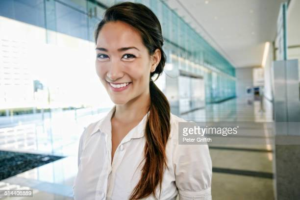 Mixed race businesswoman smiling in lobby