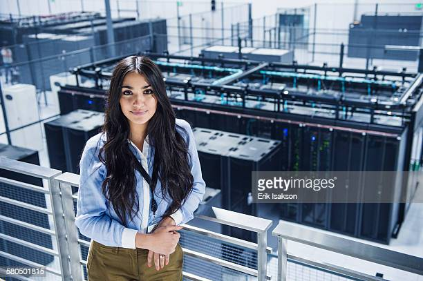 Mixed race businesswoman smiling on balcony over server room