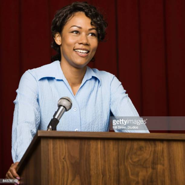 Mixed race businesswoman speaking at podium