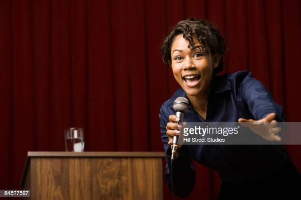 Mixed race businesswoman speaking on stage