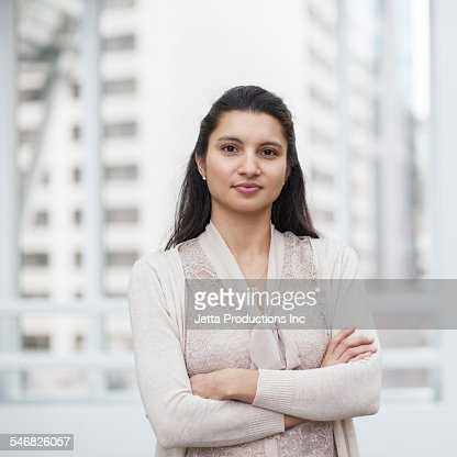 Mixed race businesswoman standing with arms crossed