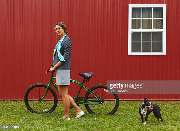 Mixed race businesswoman standing with bicycle and dog