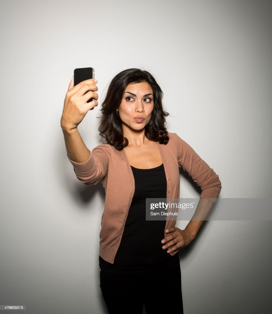 Mixed race businesswoman taking cell phone picture : Photo
