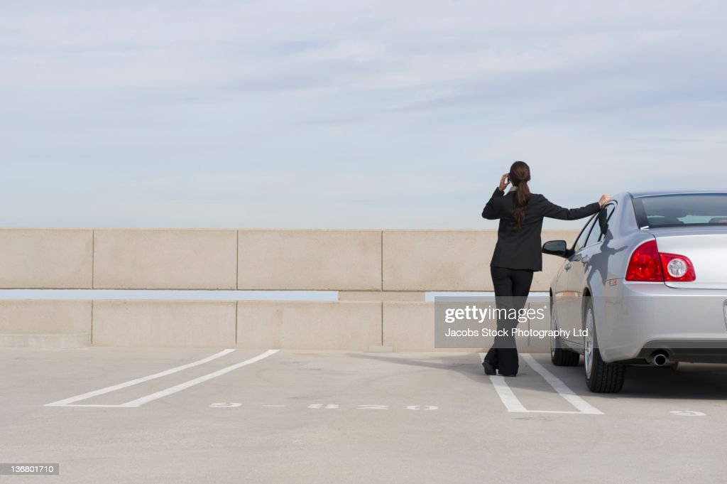 Mixed race businesswoman talking on cell phone in parking lot : Stock Photo