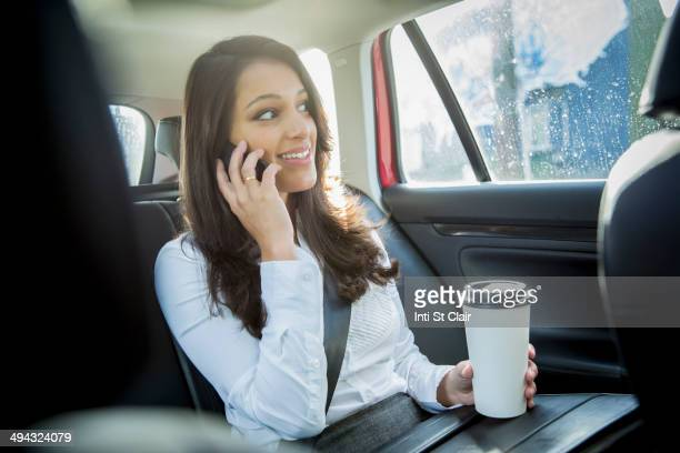 Mixed race businesswoman talking on cell phone in taxi