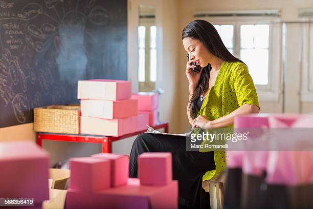 Mixed race businesswoman talking on telephone in office