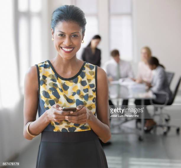 Mixed race businesswoman texting on cell phone in office