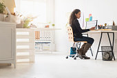 Mixed race businesswoman using cell phone at desk