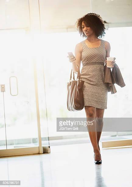 Mixed race businesswoman using cell phone in lobby area